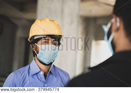 Two Construction Workers Or Engineers At Site Talking By Wearing Medical Face Mask While Maintaining