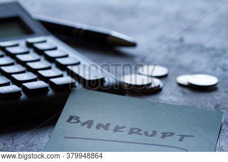 Financial Failure, Bankruptcy Concept. Coins, Calculator, Pen And Inscription Bankrupt On Dark Backg