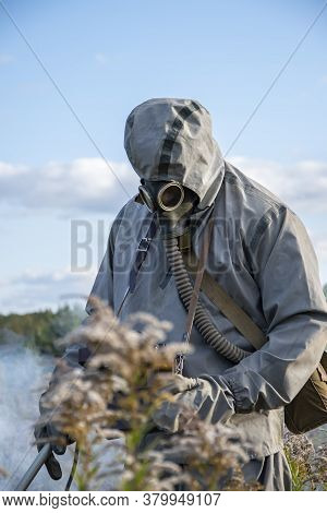 A Military Troops In A Costume Examines Radioactive Territory Against The Sky With Clouds And Wildli