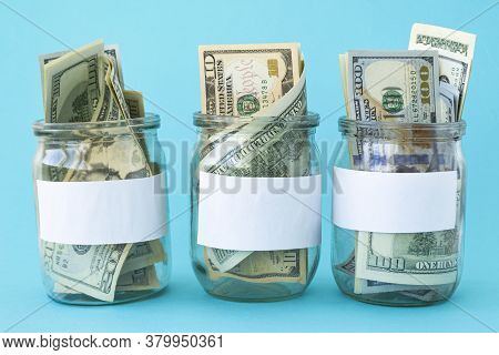 Three Piggy Bank From A Glass Jar For Life. New Dollars Sticking Out Of Piggy Banks On A Blue Backgr