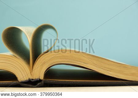 The Pages Of The Book Are Curved In The Shape Of A Heart. Opened Book On A Blue Background. Back To