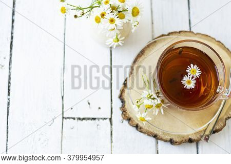 A Cup Of Chamomile And Herbal Tea With Chamomile Flowers On White Wooden Planks. A Vase Of White Flo