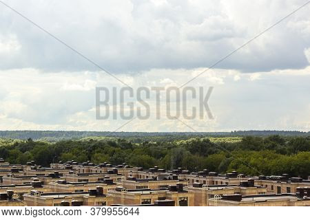 The Roofs Of Country Houses In A Forest Landscape Against A Blue Sky With Clouds. Residential Comple
