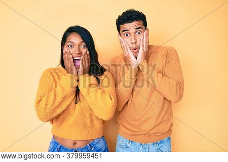 Beautiful latin young couple wearing casual clothes together afraid and shocked, surprise and amazed expression with hands on face