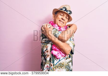 Senior handsome grey-haired man on vacation, wearing summer look with Hawaiian lei flowers hugging oneself happy and positive, smiling confident. Self love and self care