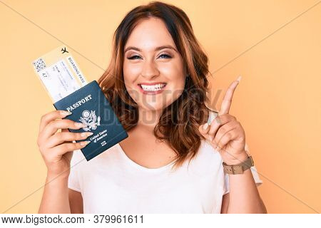 Young beautiful caucasian woman holding boarding pass and passport surprised with an idea or question pointing finger with happy face, number one