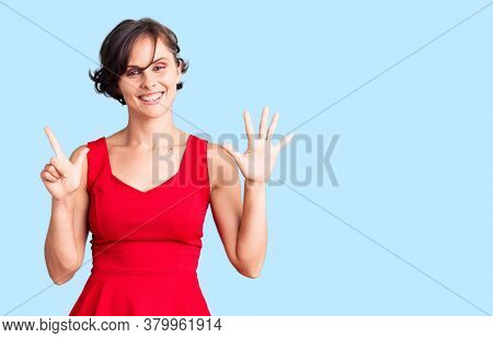 Beautiful young woman with short hair wearing casual style with sleeveless shirt showing and pointing up with fingers number seven while smiling confident and happy.