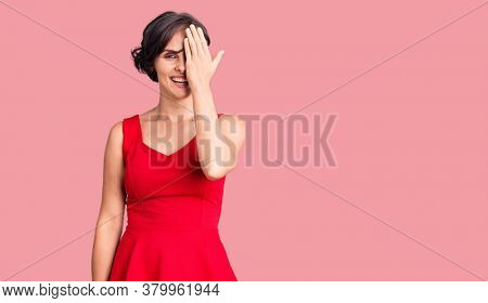 Beautiful young woman with short hair wearing casual style with sleeveless shirt covering one eye with hand, confident smile on face and surprise emotion.
