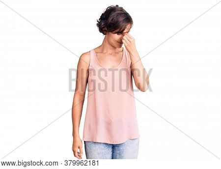 Beautiful young woman with short hair wearing casual style with sleeveless shirt tired rubbing nose and eyes feeling fatigue and headache. stress and frustration concept.