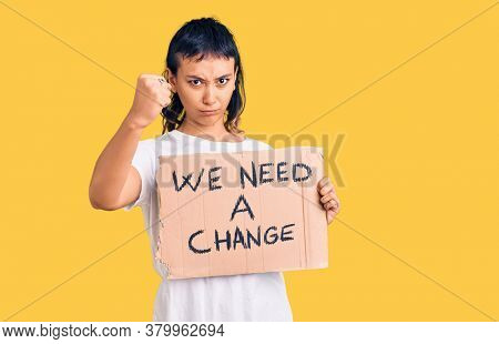 Young woman holding we need a change banner annoyed and frustrated shouting with anger, yelling crazy with anger and hand raised