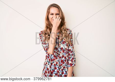 Young caucasian woman with blond hair wearing summer dress smelling something stinky and disgusting, intolerable smell, holding breath with fingers on nose. bad smell