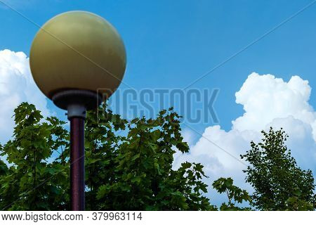 Landscape, Lamppost Against The Background Of Clouds And Trees.