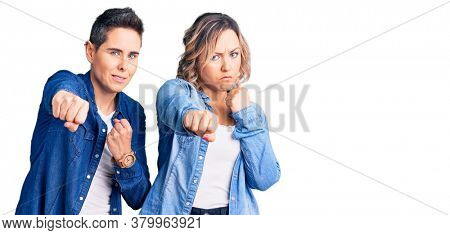 Couple of women wearing casual clothes punching fist to fight, aggressive and angry attack, threat and violence