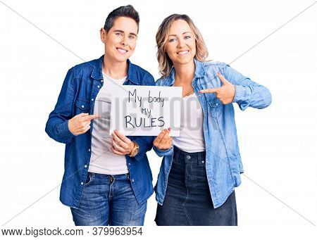 Couple of women holding my body my rules banner smiling happy pointing with hand and finger