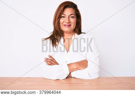 Middle age brunette hispanic business woman wearing casual white shirt sitting on the table happy face smiling with crossed arms looking at the camera. positive person.