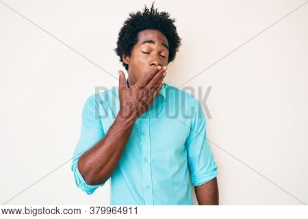 Handsome african american man with afro hair wearing casual clothes bored yawning tired covering mouth with hand. restless and sleepiness.