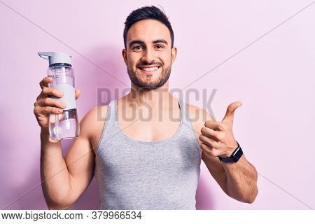 Young handsome sportsman with beard wearing sleeveless t-shirt drinking bottle of water smiling happy and positive, thumb up doing excellent and approval sign
