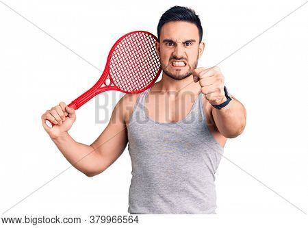 Young handsome man holding tennis racket annoyed and frustrated shouting with anger, yelling crazy with anger and hand raised