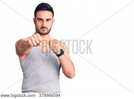 Young handsome man wearing swimwear and sleeveless t-shirt punching fist to fight, aggressive and angry attack, threat and violence