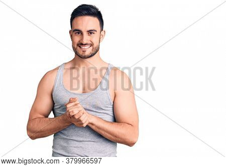 Young handsome man wearing swimwear and sleeveless t-shirt with hands together and crossed fingers smiling relaxed and cheerful. success and optimistic