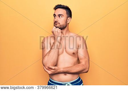 Young handsome man with beard wearing sleeveless t-shirt standing over yellow background serious face thinking about question with hand on chin, thoughtful about confusing idea