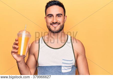 Handsome man with beard wearing sleeveless t-shirt drinking glass of healthy orange juice looking positive and happy standing and smiling with a confident smile showing teeth
