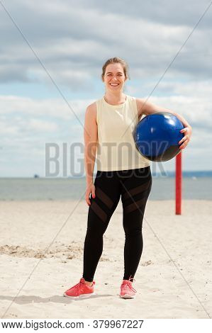 Athletic Woman With Medicine Ball At Outdoor Fitness Gym. Female Athlete Training During Beach Worko