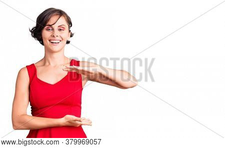 Beautiful young woman with short hair wearing casual style with sleeveless shirt gesturing with hands showing big and large size sign, measure symbol. smiling looking at the camera. measuring concept