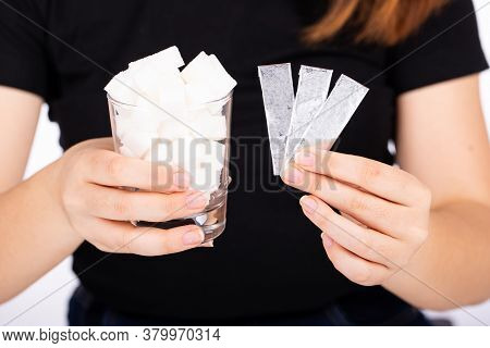 A Woman Holds A Glass Of White Sugar In One Hand, A Piece Of Chewing Gum In The Other