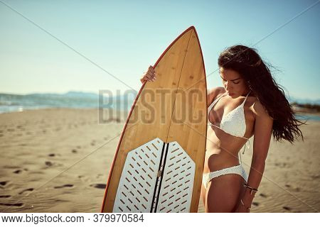 Attractive surf girl posing on the beach with surfboard