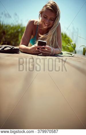 Portrait of a young woman sunbathing while texting on the dock
