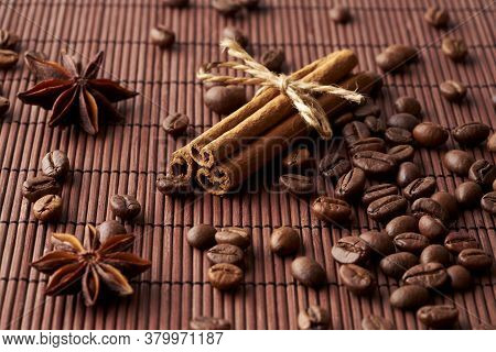 Roasted Whole Coffee Beans, Tied Sticks Of Cinnamon And Anise On A Dark Background