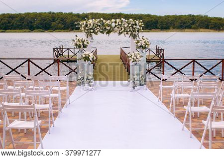 A Wedding Ceremony, A Wedding Arch, A Wedding Arch Of Twigs, Flowers And Greenery Stands On The Bank