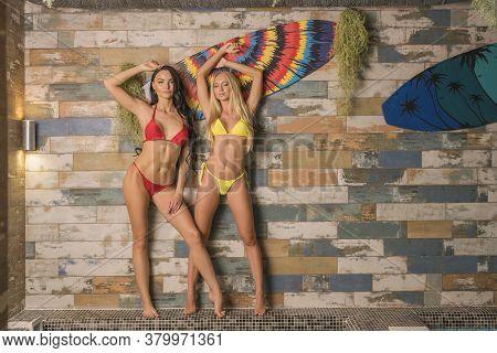 Sensual Slim Ladies In Swimwear With Arms Raised On Poolside
