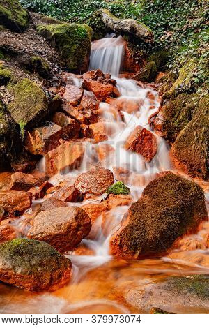 Detail Of The Mineral Springs. Cascade On Stream Of Mineral Water With Ferric Sediment On Green Moss