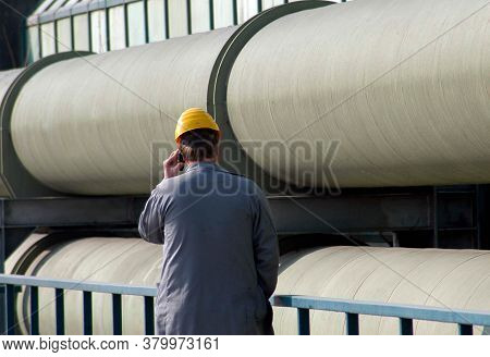 Man In Working Clothes On The Telephone In Front Of District Heating Pipelines For Heat Transportati