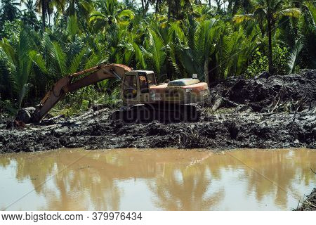 Thailand, Phuket - December 15, 2019: An Excavator Is Standing In The Mud. Excavator On A Road Const