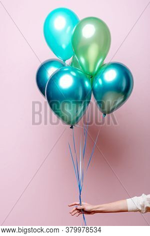 Composition Of Light Green, Green, Emerald Helium Balloons In The Hand Of A Woman On A Pink Backgrou