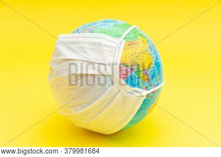Terrestrial Globe Model With White Surgical Mask Isolated On Yellow Background. Concept: Planet Eart