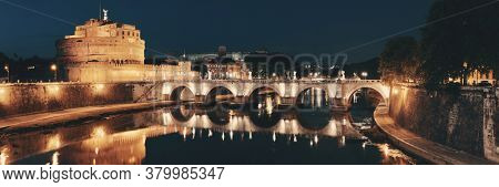 Castel Sant Angelo and bridge over River Tiber at night in Rome panorama, Italy.
