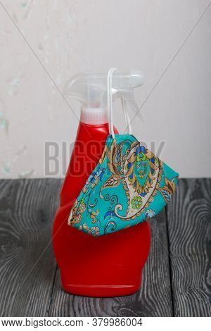 Red Plastic Bottle With Spray. Cleaning Spray. Next To The Face Mask To Protect Against The Virus.