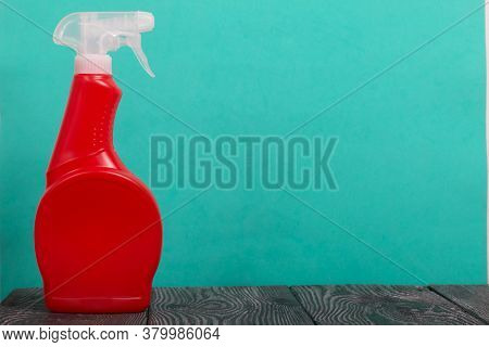 Red Plastic Bottle With Spray. Cleaning Spray. On A Mint Background.