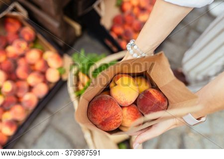 Unrecognizable Woman Hands Holding Paper Bag With Organic Peaches Outdoors At Farmers Market.