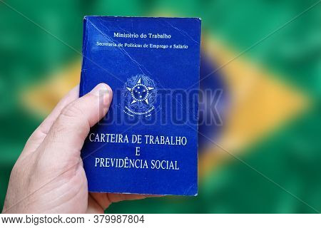 Man's Hand Holding Brazilian Work Card Isolated On Brazilian Flag Defocused Background. Written In P