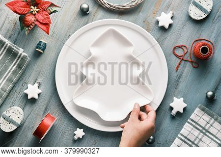 Christmas Background In Grey, Red And White With Hand Holding Plate On Table. Geometric Flat Lay Wit