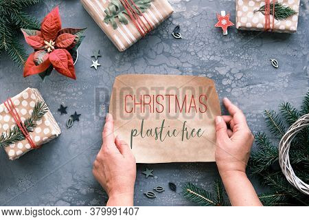 Flat Lay On Grey Table With Xmas Gifts Wrapped In Brown Paper. Text Christmas Plastic Free On Piece