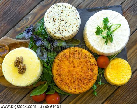Cheese Heads With Cheeses Of Different Kinds. Assortment Of Different Cheese Types On An Old Wooden