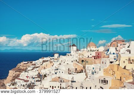 Clouds Fly Over White Houses And Old Windmill In Oia Village On Santorini, Greece