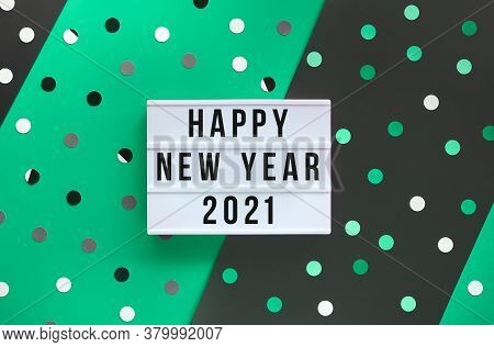 Light Box With Text Happy New Year 2021. Layered Green And Black Paper With Confetti, Polka Dots.