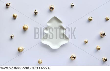 Golden Trinkets, Christmas Baubles Around Plate Shaped As Xmas Tree On White Paper. Trendy Minimal S